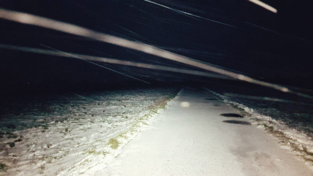 An image taken in the dark with a headtorch of a snow covered path with snow trails blowing across the picture.