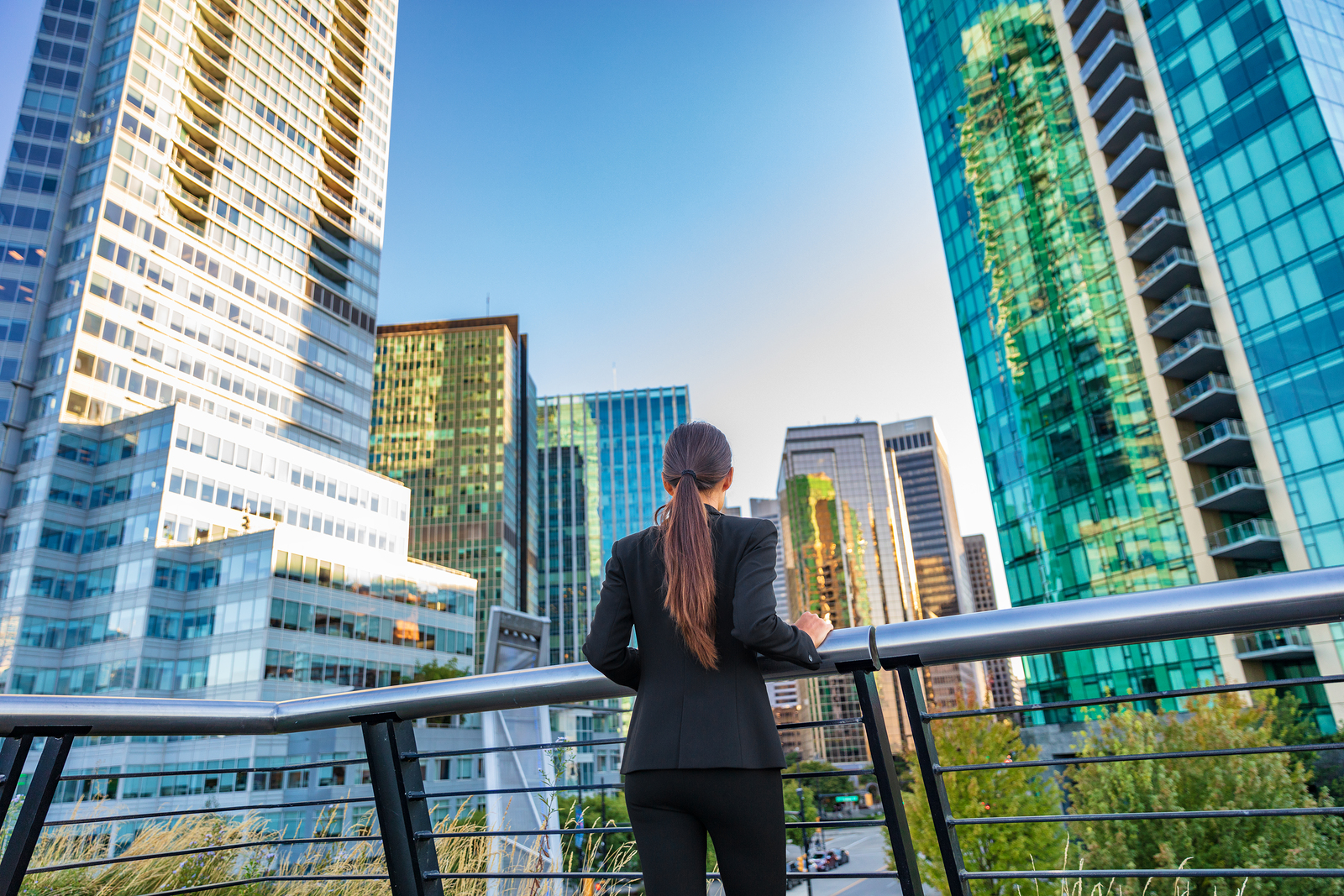 Business woman in city center looking at view of skyline skyscrapers.