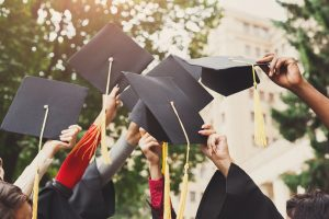 A group of students celebrating their graduation by throwing caps in the air close-up.
