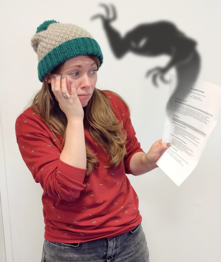 OU Career Consultant Penny Beecroft holding a CV with a ghost emerging from it.
