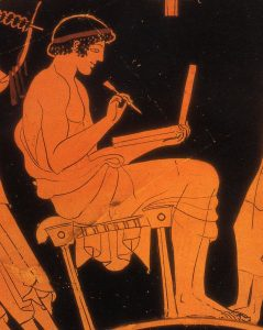 boy writing on a wax tablet, as shown on a Greek vase