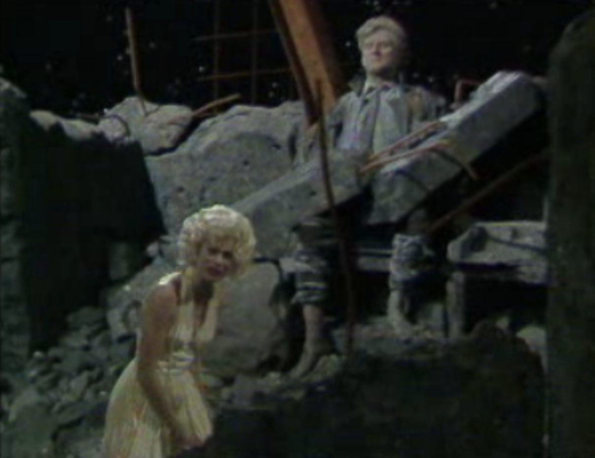 Io is shown visiting Prometheus and telling the story of her torment by Zeus who sent gadflies to pursue her round the world. Played by Julia Hills, Io was costumed as a Marilyn Monroe look-alike. Ancillary material to the course included a video clip of Marilyn Monroe singing 'Happy Birthday Mr President' at a birthday party held for President John F Kennedy.