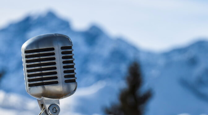 Image of a microphone set against mountains