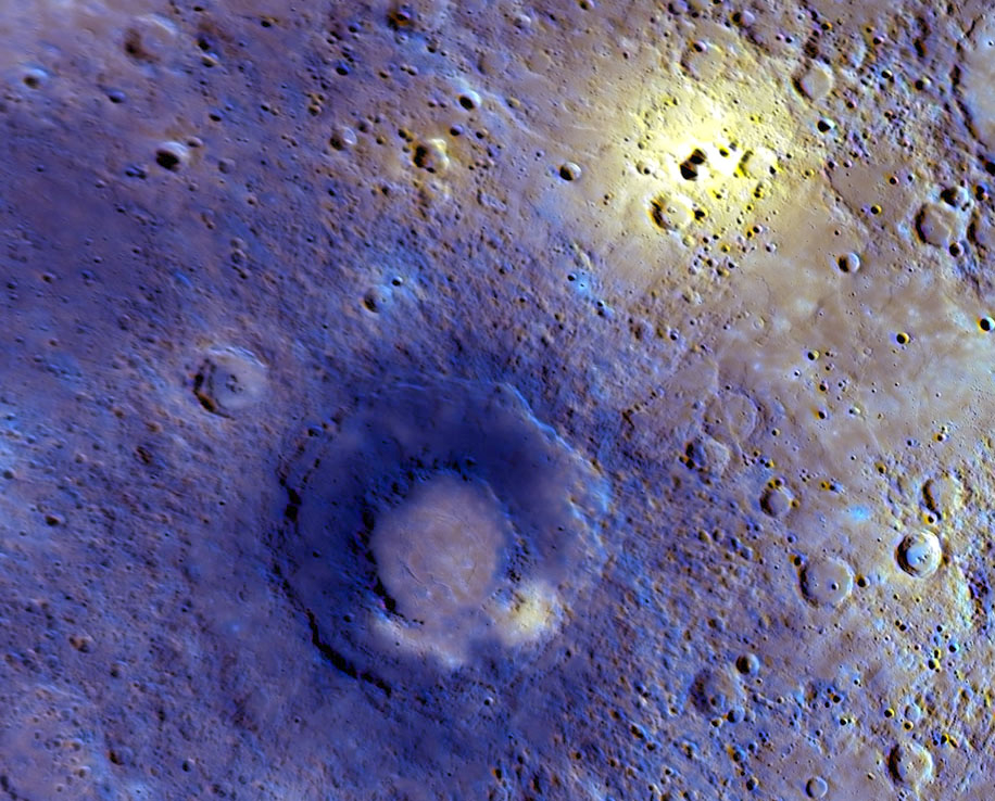 910 km MESSENGER view of Mercury. The large yellow spot at top right is a deposit from an explosive volcanic eruption from the deeply-shadowed vent at its centre. The smaller yellow spot in below the middle of the frame is a similar deposit, from a vent too small to make out. (NASA/JHUAPL/CIW)