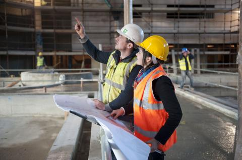 man and woman (in safety apparel) at construction site; man pointing ahead at something