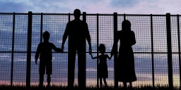 Image: Silhouette of refugee family in front of fence