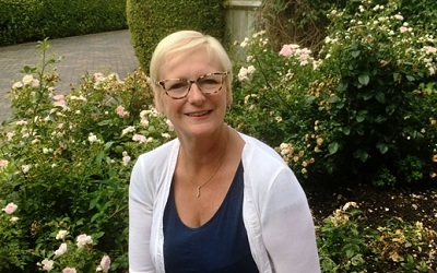 Photo of Peta Wilkinson, Cheif Executive of Willen Hospice, smiling infront of flowers. She has short blonde hair, a white cardigan and funky leopard print glasses on
