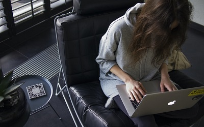 Photo shows a woman with long hair on her laptop, wearing a grey hooded top. She is sitting in a leather chair