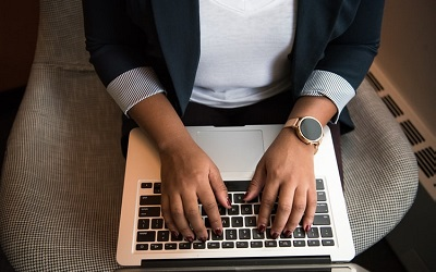 Photo of a woman's hands on a laptop, typing. She is wearing a blazer and smart gold watch