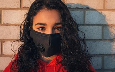Photo shows a woman with curly, dark hair standing against a brick wall staring into the camera. She has very dark brown eyes and wears a black mask and a red jumper. Photo credit: Gayatri Malhotra, Unsplash