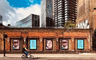 Photo by Étienne Godiard on Unsplash - images shows a cyclist riding past charity adverts on a brick wall in London. The wall looks run down and tired and behind it, beautiful modern, imposing sky scrapers. The image reflects the challenges faced by charities and the disparity between the support the private sector has received during the pandemic and the limited support the voluntary sector has received