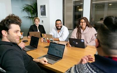 A team sit around a table with laptops in a meeting. They look happy