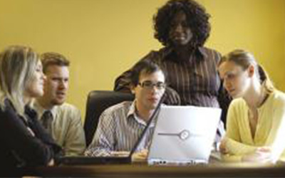 A group of people gathered around a laptop