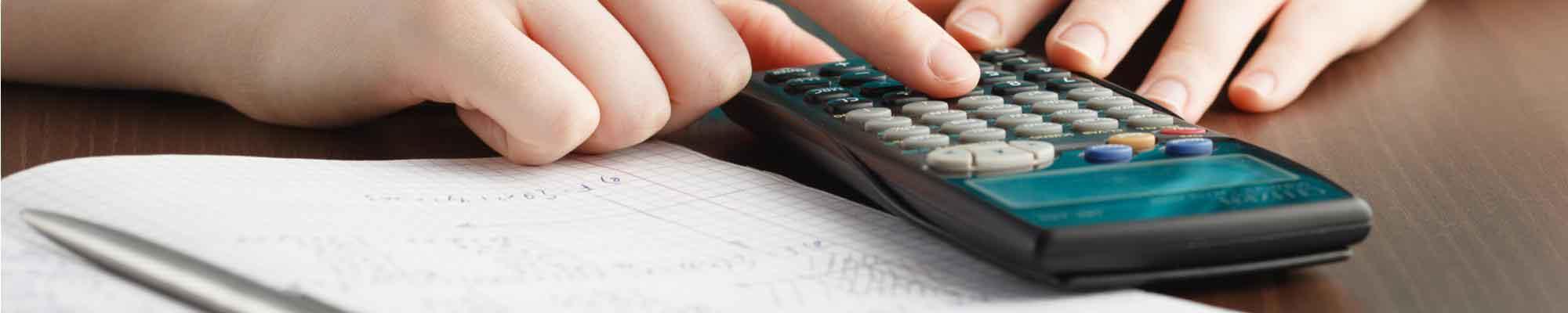 A mathematics student using a calculator and hand-writing mathematics