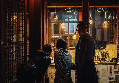Family looking in a light shop window while dark outside