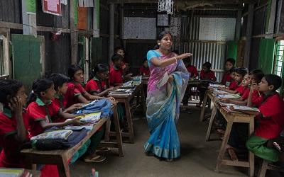 Students listen to their school teacher, Shuma Das during class at the Sahabatpur Daspara Ananda school in Sahabatpur village, Bangladesh on October 12, 2016
