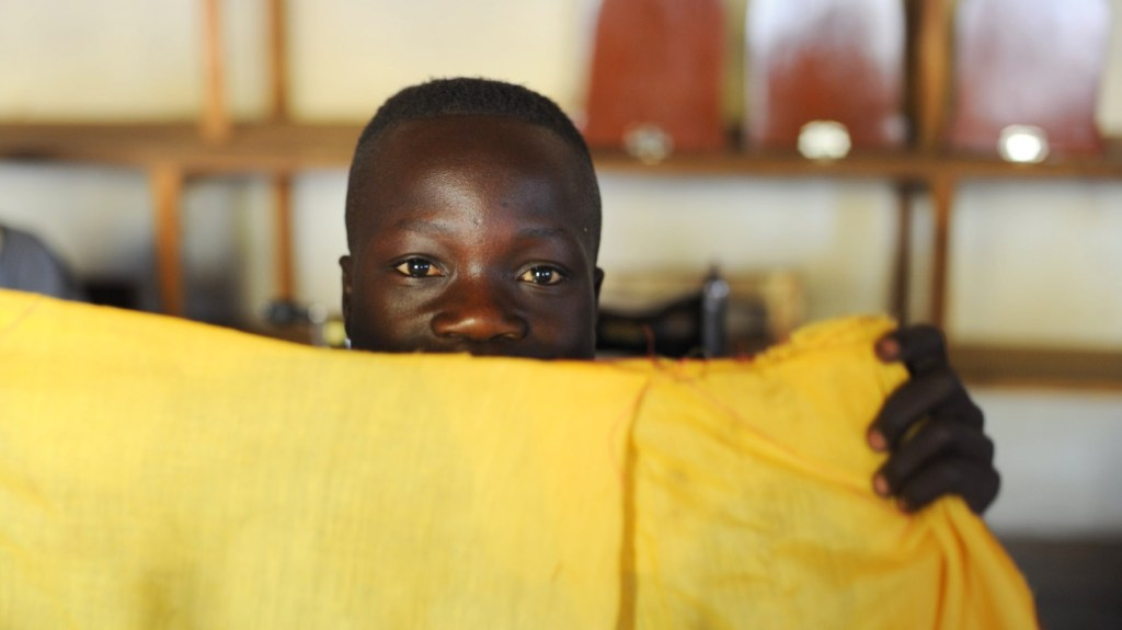 Photo taken in DRC by Julien Harneis CC BY-SA 2.0 - child holding a yellow sheet