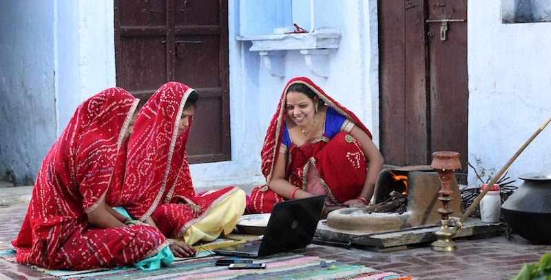 Photo of three women wearing identical saris gathered round a laptop