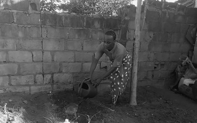 """Photo shows a trans woman in Mozambique tending to her garden. She told us """"Watering my garden to show society that transwomen perform all activities like other women in their home space. I call that positive visibility"""""""