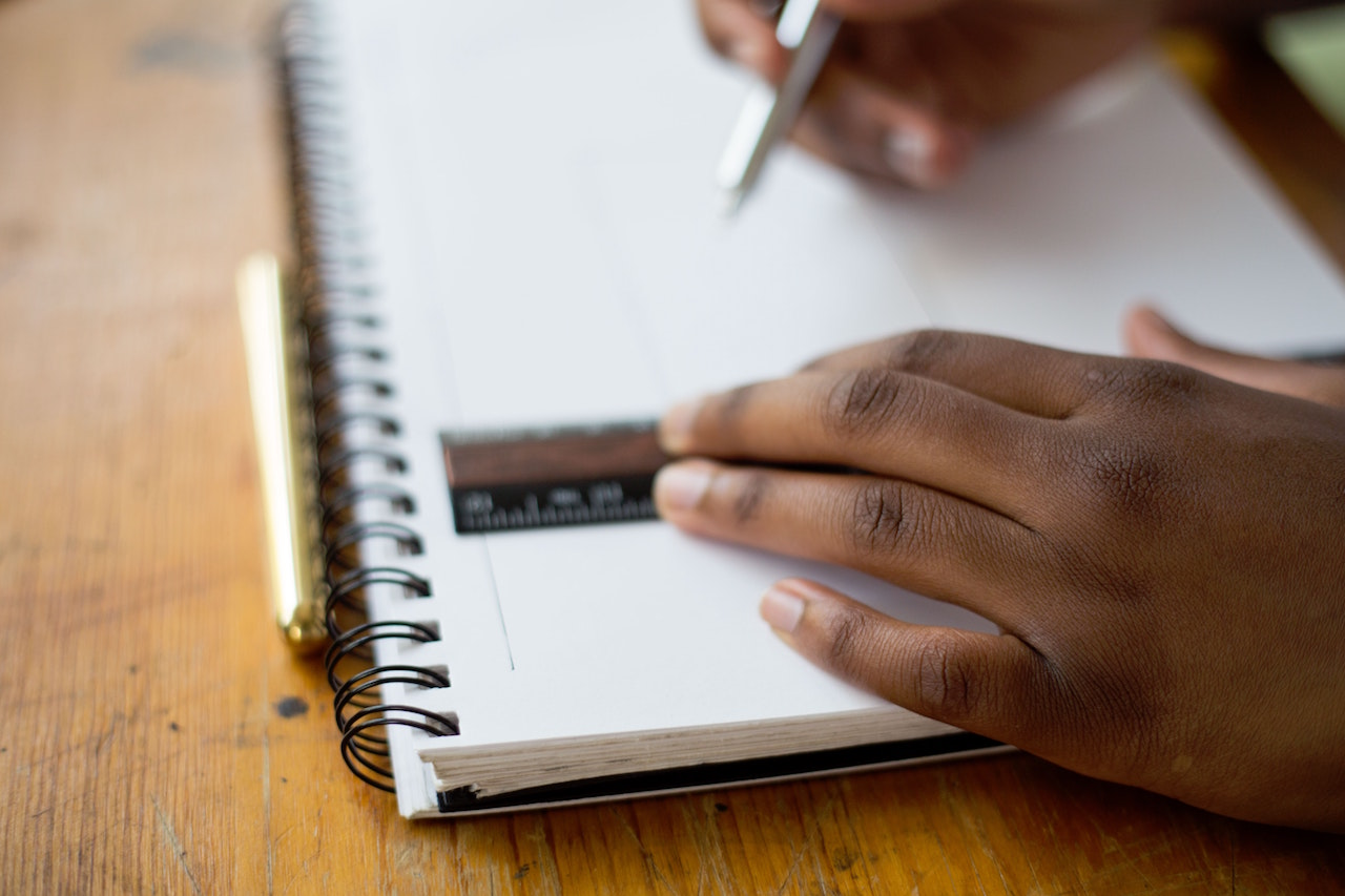 Photo of student's hands with ruler, pen and notebook