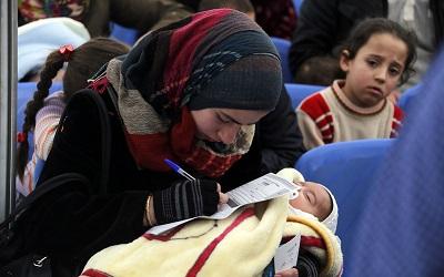 A Syrian mother holding her baby, taken in Lebanon, Photo: Mohamed Azakir / World Bank