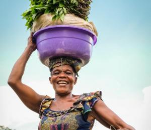 A women in DRC carrying vegetables by Axel Fassio/CIFOR, licensed under creative commons.