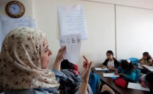 photo of teacher teaching refugee children