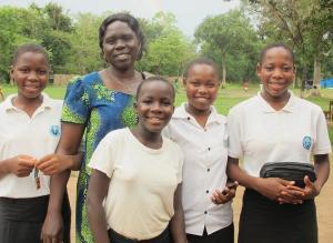 Photo of Ibba School head teacher Vicky Ajidiru with 4 students