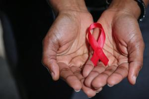 Photo of hands holding pink AIDS awareness day ribbon