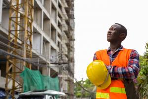photo of construction worker looking up at building in progress