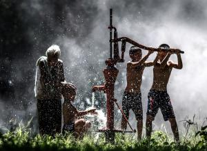 photo of boys and grandmother at a water pump in Thailand