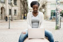 Image of a woman sitting on a bench using a laptop