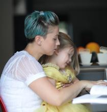 Woman searching on her laptop with a little girl on her lap