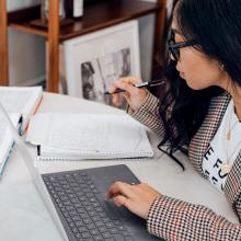 A student is sitting at a table with their hand on the keyboard of an open laptop computer. There is a notebook next to the laptop and the student is holding a pen, ready to write in the notebook.