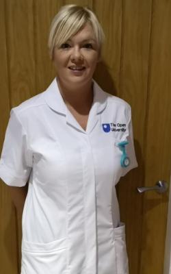 Leona in her OU student nurse uniform standing in front of a wooden door.