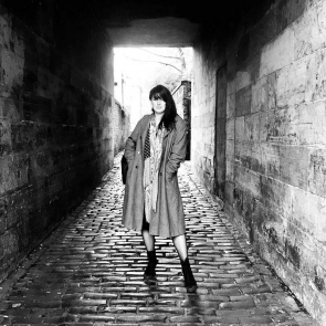 A white woman with long dark hair stands on a cobbled lane. The stone buildings around her form an archway overhead. She is wearing a long coat and boots.