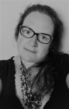 Monochrome picture of Helen Bowes-Catton, a white woman in her early forties. She is wearing glasses and has long dark hair.