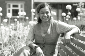 Kesi Mahendran sat in the Open University legacy garden in front of her office