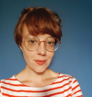 profile picture of marie thompson, wearing round framed glasses and stripey red top against a blue background