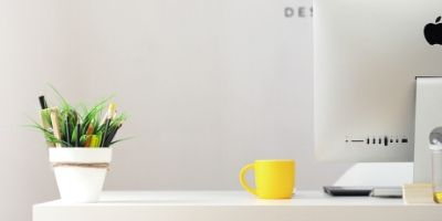 A clean white desk with a plant pot full of pens, a yellow mug and part of an iMac computer in view.