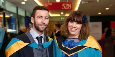Two students smiling to camera after an OU degree ceremony at Croke Park