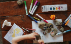 A desk with crayons, rocks, paints and paper all being used.