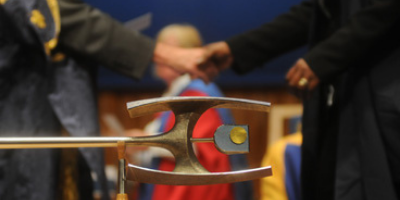 Two people shaking hands behind a pole at an OU degree ceremony