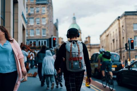 A young man walking through the city centre with headphones on.