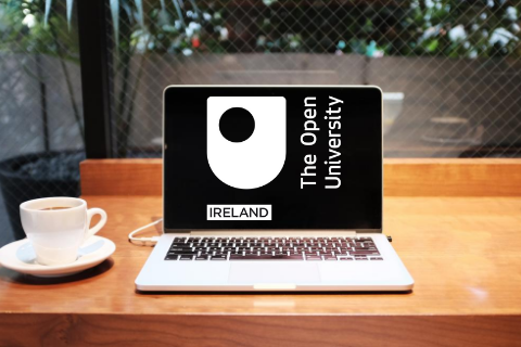 A laptop with the OU in Ireland logo and a cup of coffee on a desk