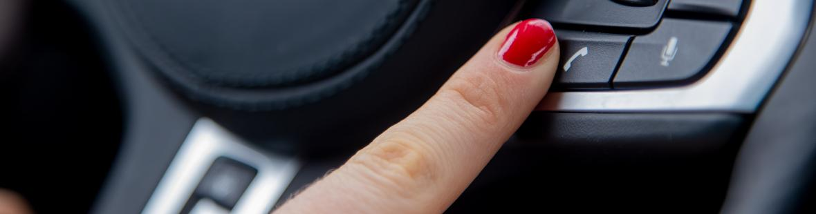 Finger on phone button on a steering wheel
