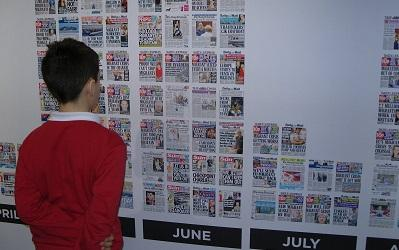 Photo of young boy reading the wall of hateful headlines at the Migration Museum in London (c) Heidi McCafferty
