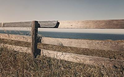 Image of a fence next to the sea representing a country's border