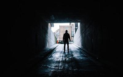 Person walking through a dark tunnel