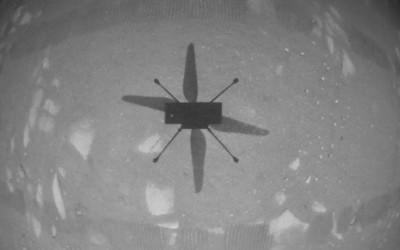NASA's Ingenuity Mars Helicopter hovers over the Martian surface. NASA